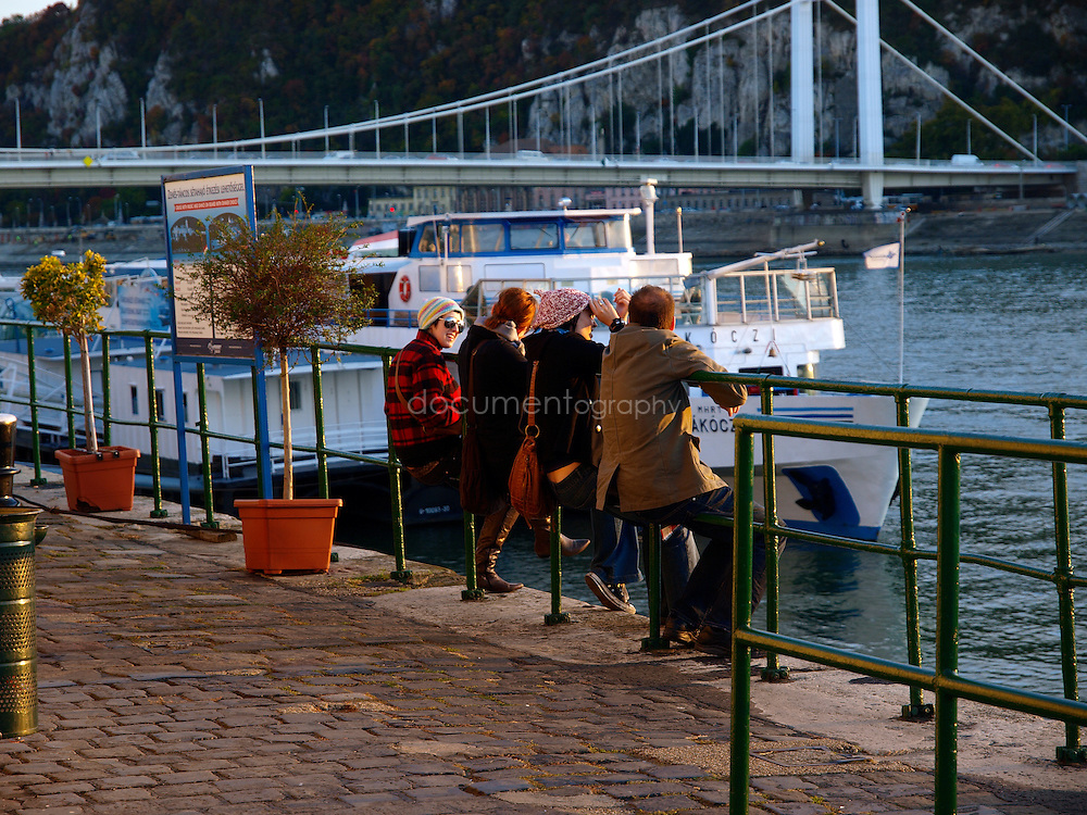 Tourists rest and chat on the banks of the Danube river as the sun sets, Budapest, Hungary.