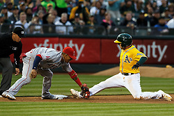 OAKLAND, CA - JUNE 17:  Jed Lowrie #8 of the Oakland Athletics slides into third base ahead of a tag from Yunel Escobar #6 of the Los Angeles Angels of Anaheim during the fourth inning at the Oakland Coliseum on June 17, 2016 in Oakland, California. (Photo by Jason O. Watson/Getty Images) *** Local Caption *** Jed Lowrie; Yunel Escobar
