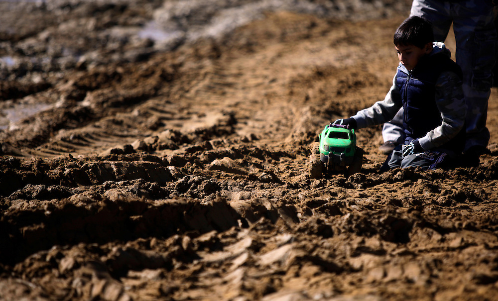 A child plays with a toy truck in the mud at the Redneck Yacht Club in Punta Gorda, Fla. Photo by: Greg Kahn
