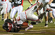 Iowa City High's Xavier Washpun (27) is pulled down by Linn-Mar's Andrew Gassmann (23) during during the game between the Iowa City High Little Hawks and the Linn-Mar Lions at Linn-Mar Stadium in Marion on Friday October 12, 2012.
