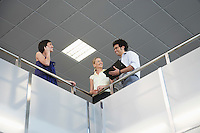 Three people standing at railing of indoor balcony