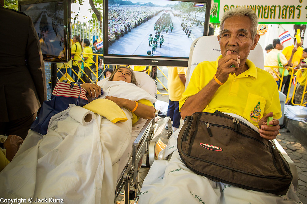 "05 DECEMBER 2012 - BANGKOK, THAILAND:  People who passed out in the heat rest in the Red Cross tent while the ""Trooping of the Colors"" is broadcast on a TV behind them on the Royal Plaza Wednesday. They were waiting to see Bhumibol Adulyadej, the King of Thailand, before his public audience at the Mukkhadej balcony of the Ananta Samakhom Throne Hall. December 5 is a national holiday. It's also celebrated as Father's Day. Celebrations are being held across the country to mark the birthday of Bhumibol Adulyadej, the King of Thailand.   PHOTO BY JACK KURTZ"