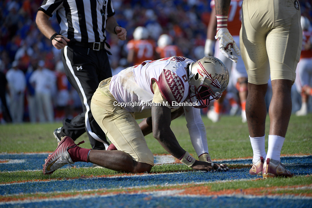 Florida State linebacker Matthew Thomas (6) pulls up a piece of turf after intercepting a pass during the second half of an NCAA college football game against Florida Saturday, Nov. 25, 2017, in Gainesville, Fla. FSU won 38-22. (Photo by Phelan M. Ebenhack)