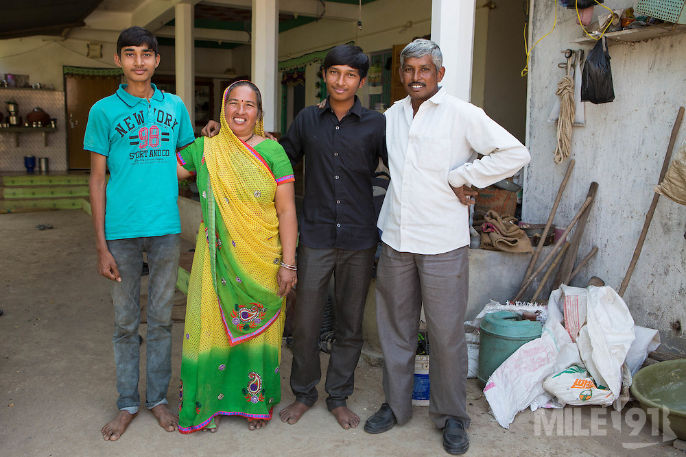 A portrait of Vallabh and his wife, Prabhaben, and their two children in front of their home in Ahmedabad, India.<br /> <br /> They have recently installed some drip irrigation on their farm and are not only seeing some real improvements in their cotton plants but it's also saving them a lot of water and time. This is enabling them to grow other vegetables.
