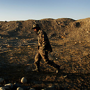 A Northern Alliance fighter walks behind a hill shielding him from Taliban artillery in this photo on October 7, 2001.