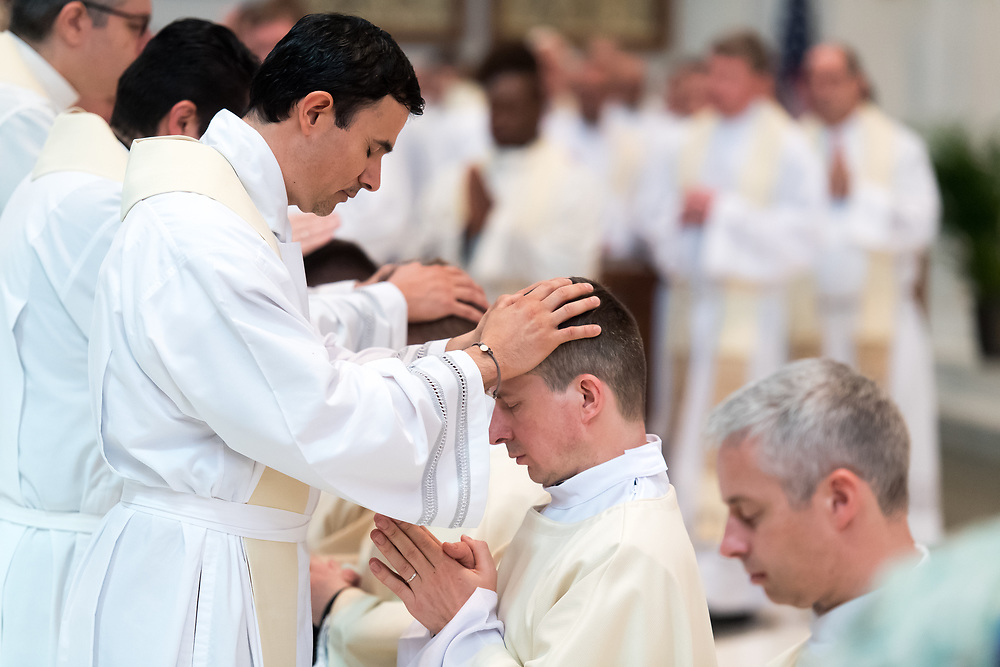 DENVER, CO - MAY 13: Bogusław Rębacz (second from left) prays as priests lay their hands upon him during his ordination to the priesthood at the Cathedral Basilica of the Immaculate Conception on May 13, 2017, in Denver, Colorado. (Photo by Daniel Petty/for Denver Catholic)
