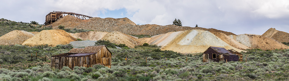 "Orange-yellow mine tailings cover hillsides above ramshackle cabins at Bodie, California's official state gold rush ghost town. Bodie State Historic Park lies in the Bodie Hills east of the Sierra Nevada mountain range in Mono County, near Bridgeport, California, USA. After W. S. Bodey's original gold discovery in 1859, profitable gold and silver ore discoveries in 1876 and 1878 transformed ""Bodie"" from an isolated mining camp to a Wild West boomtown. By 1879, Bodie had a population of 5000-7000 people with 2000 buildings. At its peak, 65 saloons lined Main Street, which was a mile long. Bodie declined rapidly 1912-1917 and the last mine closed in 1942. Bodie became a National Historic Landmark in 1961 and Bodie State Historic Park in 1962. This panorama was stitched from 5 overlapping photos."