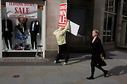 During a windy afternoon, a sandwich board man holds on to his breaking sign for a menswear shop's closure sale.