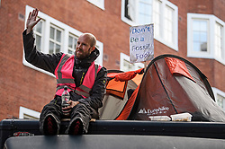 © Licensed to London News Pictures. 08/10/2019. London, UK. An Extinction Rebellion activists sat on top of a lorry outside the Department for Environment, Food and Rural Affairs in Westminster. Activists have converged on Westminster for a second day, blockading roads in the area and calling on government departments to 'Tell the Truth' about what they are doing to tackle the Emergency. Photo credit: Ben Cawthra/LNP