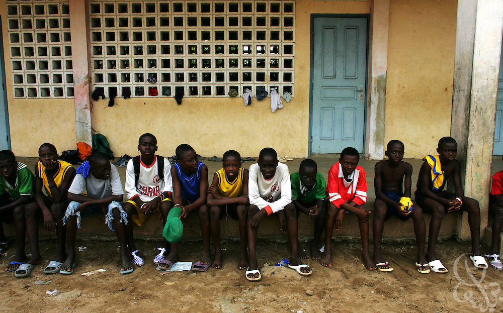 Ivorian boys watch as others train at the Olympic Sport Abobo club in the Abobo neighborhood of Abidjan, Côte d'Ivoire February 18, 2006. Motivated by the success of the national team, and Ivorian footballers in European leagues, Ivorian boys and their parents often view football as their only chance to escape poverty within their communities.