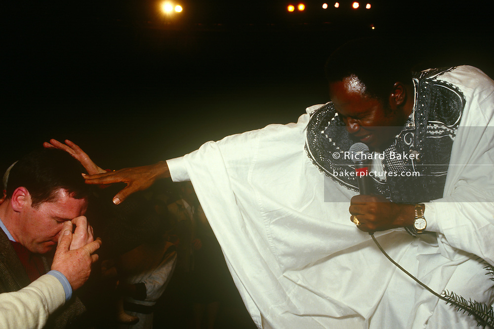 Nigerian evangelist, Rev. Benson Idahosa places his hand on the head of a Born-again Christian during a Christian rally at Butlins Bible Week during Easter in 1986 at Minehead, England. Benson Andrew Idahosa (1938 -1998) was a Charismatic Pentecostal preacher, and founder of the Church of God Mission International with headquarters in Benin City, Nigeria.