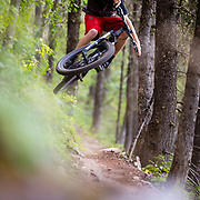 Andrew Whiteford gets air along the singletrack of the Ferrin's Trail in Jackson, Wyoming.