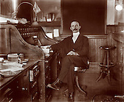 Well dressed man with a mustach seated in an office, circa 1900 There is an American flag on top of his rolltop desk. jobs, men, office, work