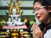24 AUGUST 2015 - BANGKOK, THAILAND: A woman prays at a memorial service for victims of the Erawan Shrine bombing. One week after the a bomb at the Erawan Shrine in the center of Bangkok killed dozens and hospitalized scores of people, police have not made any arrests. Police bomb sniffing dogs have been deployed to malls and markets around Bangkok. There was a large memorial service sponsored by businesses close the bomb site Monday evening.     PHOTO BY JACK KURTZ