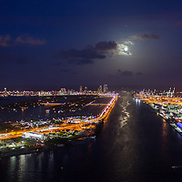 Aerial view of the Port of Miami and Government Cut with the full moon over Miami Beach.