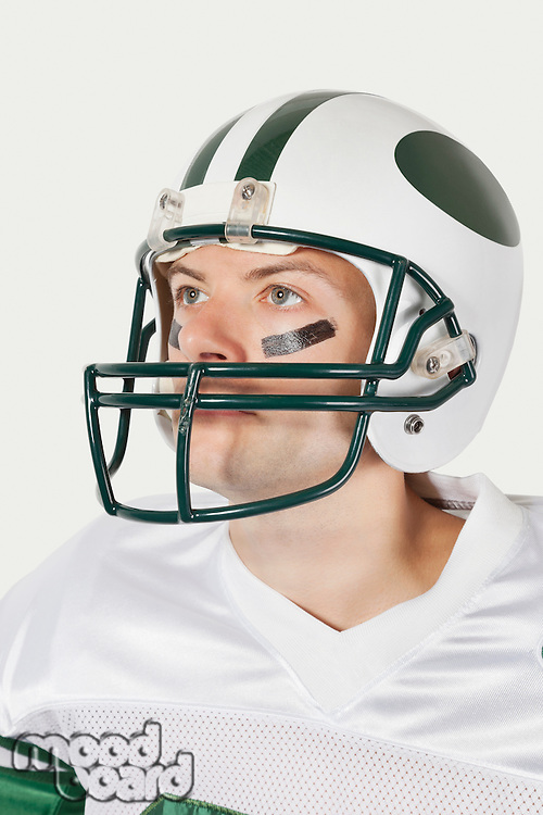 Young man in football uniform looking away against gray background
