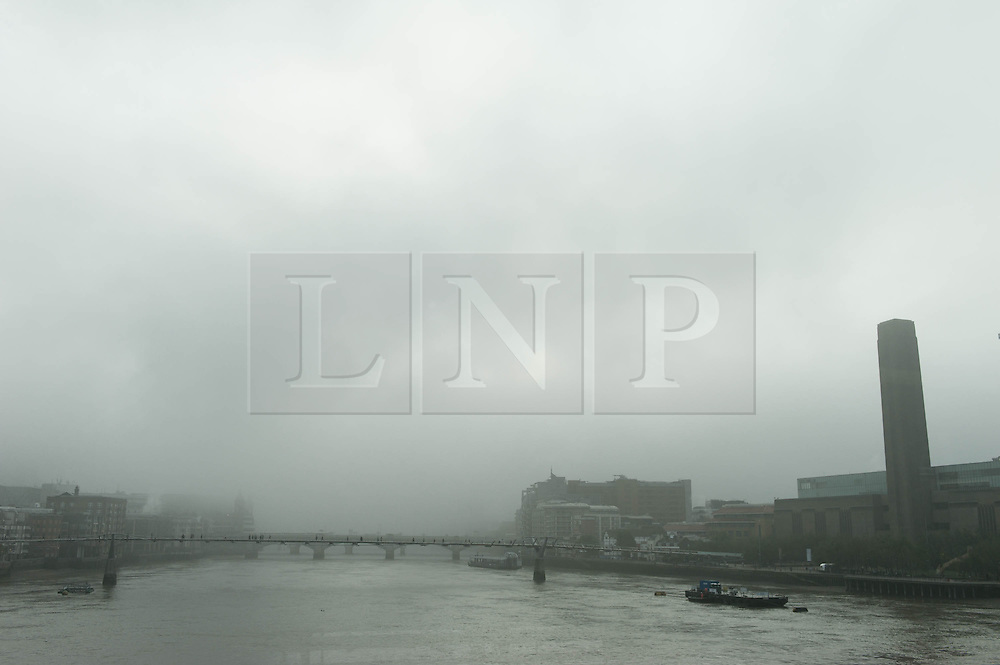 © Licensed to London News Pictures. 24/09/2013. London, UK. A heavy fog totally obscures The Shard building and shrouds the River Thames and Tate Modern as commuters make their way to work in the morning across the Millennium Bridge.   Photo credit : Richard Isaac/LNP