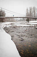 A woman crossing the Tawks-Foster suspension bridge over the Methow river near Mazama, Washington, USA.