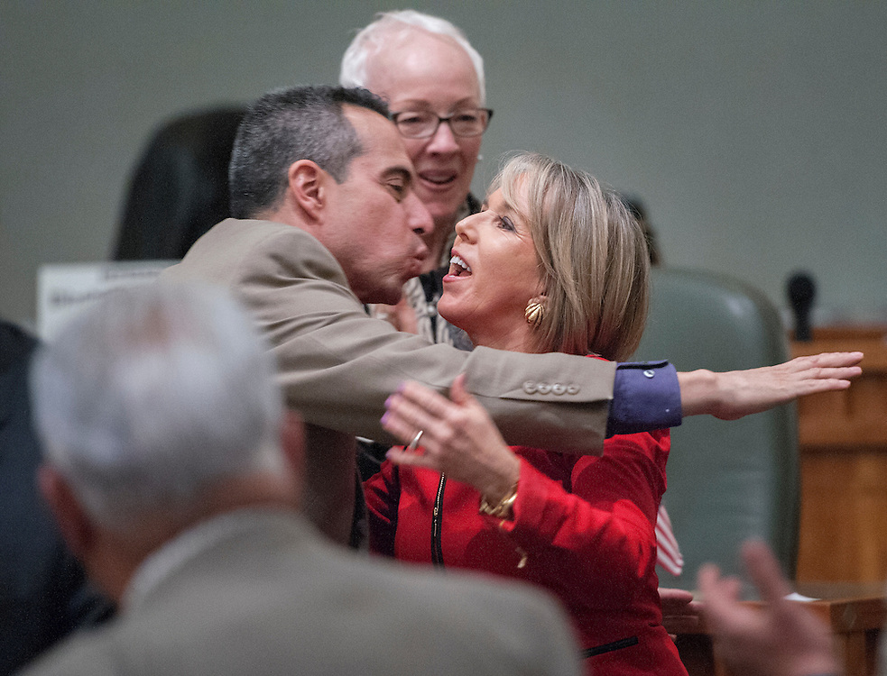 "em012617e/a/U.S. Rep. Michelle Lujan Grisham, right, is greeted by Rep. Antonio ""Moe"" Maestas, D-Albuquerque, left, and Rep. Gail Chasey, D-Albuquerque, behind them, as she enters the House chambers to speak to a joint session of the House and Senate in Santa Fe Thursday January 26, 2017.  (Eddie Moore/Albuquerque Journal)"