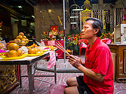 "19 FEBRUARY 2015 - BANGKOK, THAILAND:  A man prays at a Chinese shrine on Chinese New Year in Bangkok. 2015 is the Year of Goat in the Chinese zodiac. The Goat is the eighth sign in Chinese astrology and ""8"" is considered to be a lucky number. It symbolizes wisdom, fortune and prosperity. Ethnic Chinese make up nearly 15% of the Thai population. Chinese New Year (also called Tet or Lunar New Year) is widely celebrated in Thailand, especially in urban areas that have large Chinese populations.    PHOTO BY JACK KURTZ"