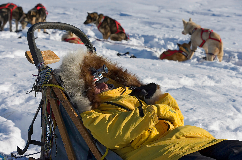 USA, Alaska, Nikolai, Musher Charlie Bouilding sleeps on top of his sled near other dog teams along trail 20 miles east of Nikolai checkpoint during 2005 Iditarod sled dog race
