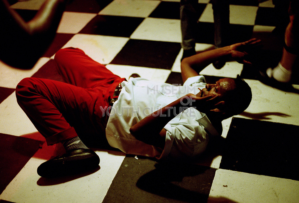Man lying on his back, pulling off some dance moves, Brazil, 2000's