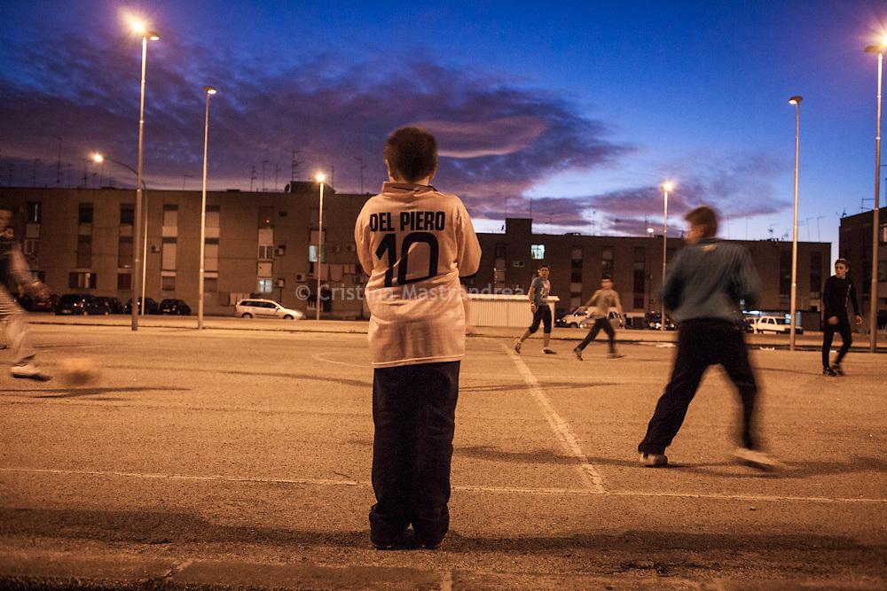 """Taranto, quartiere Tamburi """"case parcheggio"""", ragazzini giocano nel campo da calcio di cemento costruito tra le case."""