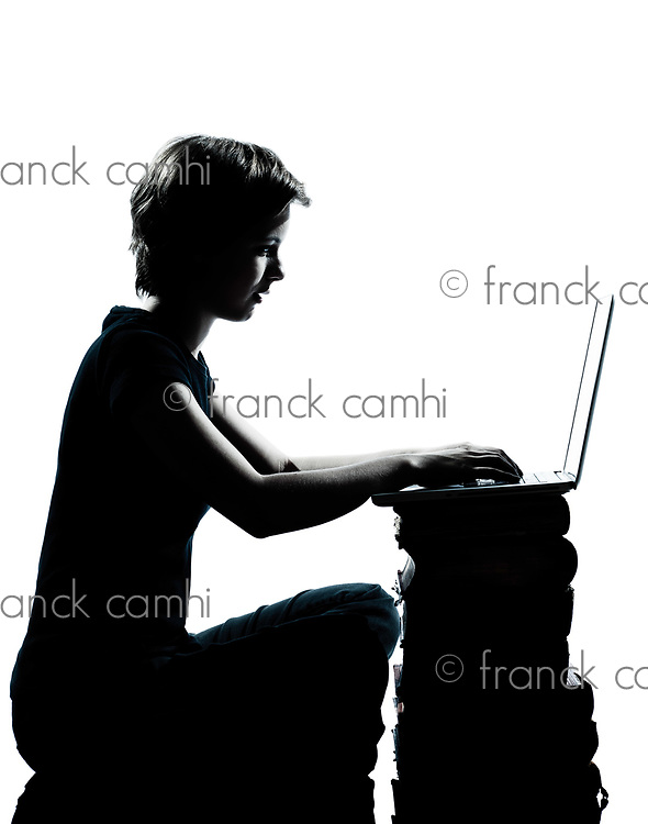 one caucasian young teenager silhouette boy or girl sitting computer computing laptop books full length in studio cut out isolated on white background