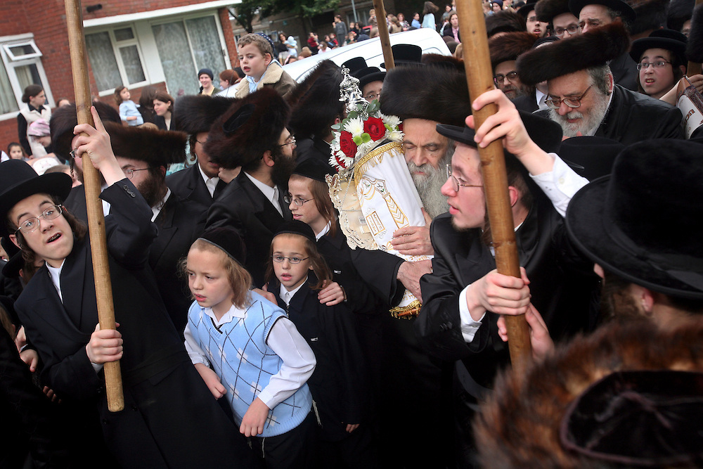 When a new Sefer Torah (five books of Moses) is completed after years of work it is carried in a big community parade to synagogue. Rabbis and leaders young and old from the Ashkenazi Nitra group take it turns to carry the decorated scrolls to their Shul on Clapton Common, Stamford Hill. Members of the community touch and kiss the scrolls as they pass.