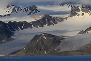 Glaciers flow from mountains to sea shrouded by clouds in Smeerenburgfjorden on the north coast of Spitsbergen island; Svalbard, Norway.