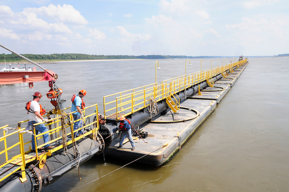 {8/24/12} {10pmCST} -JOB # 42286- Greenville , MS, U.S.A. --Workers on  the Dredge JADWIN, of the US Army Corp of Engineers, hook up the Dredge to the 1000 foot pipeline and open the pontoons to secure the pipeline so they can pump out the sludge. watches as the dredging begins 7miles downriver from Greenville MS. where the Army Corp of Engeineers is dredging the river to keep it open to tug boat traffic. Sandbars creep up as the water level drops on the Mississippi River makeing navigating the Mississippi River difficult for tug boat captains Ron Mook , Friday August 24,2012. Historically low river levels on the Mississippi River are causing havoc on river traffic: grounding barges loaded with grain and fertilizer, traffic jams several miles long and forcing the Coast Guard to close down chunks of the river due to groundings. The area around Greenville, Miss., has closed three times the past week due to groundings. Last year, there were five total groundings the entire low-water season. Locals who fought historic high-water floods last year are this year engaged in a different fight: keeping barges afloat on a vanishing Mississippi.  -- Photo by Suzi Altman, Freelance.