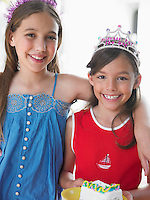 Portrait of two girls (7-9 10-12) in tiaras smiling