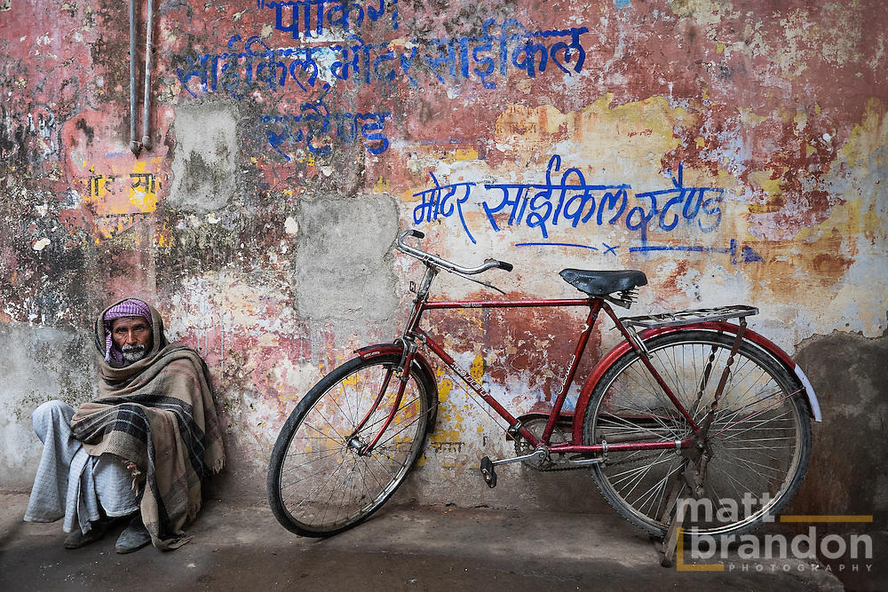 "An Indian man sits against the wall by his bike. The writing on the wall read ""bicycle parking here""."