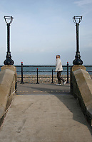 woman walking along the seafront in the winter at the seaside town of Bray in Wicklow Ireland