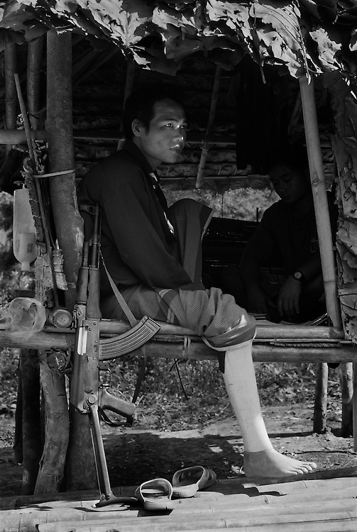 Maung Kyaw, a KNLA guerrilla, in an outpost that protects the Lep Per Her camp from attack by the SPDC and DKBA. <br /> <br /> He has been a soldier for nine years and lost his leg after stepping on a landmine five years ago, while fighting the Burmese military on the frontline.<br /> <br /> Thai/Burma border 2004.<br /> <br /> (Please see Galleries for further information).