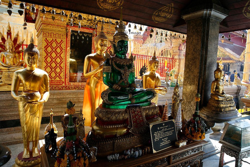 Chiang Mai, Wat Phrathat Doi Suthep, shrine with several Buddha statues, one of green clear plastic