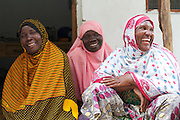 Solar engineers and members of the village energy commitee in  Chekeleni village, near Mtwara, Tanzania...left to right; Fatuma, Arafa and Fatuma..The Barefoot Solar project enables women from the poorest communities in rural Tanzania to run successful businesses by installing, repairing and maintaining solar equipment for their communities and beyond...VSO volunteer Lesley Reader project manages the scheme by liaising with the Tanzanian government, Barefoot college and the Indian government.