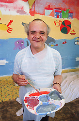 Portrait of man with learning disability holding paint palette and paint brush after painting wall mural in community centre,