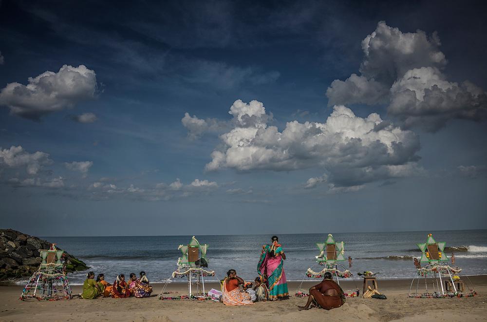 Women wait on the beach at a village-level Ganesh Chaturthi Festival in Tamil Nadu.    Tiruchchepuram, Tamil Nadu, India.