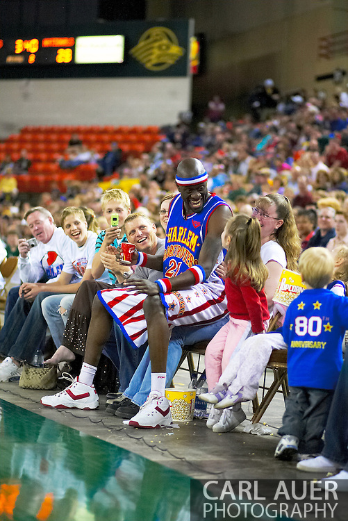 """04 May 2006: Kevin """"Special K"""" Daley talks it up with a little fan while sitting on another fan at the Harlem Globetrotters vs the New York Nationals at the Sulivan Arena in Anchorage Alaska during their 80th Anniversary World Tour.  This is the first time in 10 years that the Trotters have visited Alaska."""