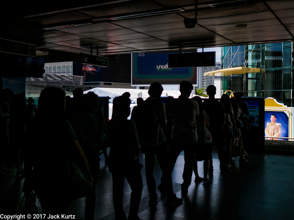 31 MARCH 2017 - BANGKOK, THAILAND: People wait in line to board the Sukhumvit line train of the BTS Skytrain in Siam Station. A portrait of Somdet Phra Chao Yu Hua Maha Vajiralongkorn<br /> Bodindradebayavarangkun, the new King of Thailand is in front of Siam Paragon, the upscale mall next to the station. He is popularly known as Maha Vajiralongkorn (Rama X).     PHOTO BY JACK KURTZ