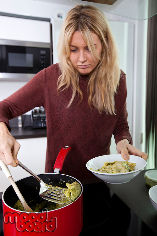 Woman serving prepared pasta in bowl at kitchen counter
