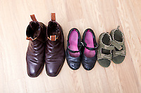 High angle view of family shoes placed in a row on hardwood floor