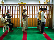13 JULY 2013 - BANGKOK, THAILAND:  Men pray during Ramadan at Haroon Mosque in Bangkok. Ramadan is the ninth month of the Islamic calendar, and the month in which Muslims believe the Quran was revealed. The month is spent by Muslims fasting during the daylight hours from dawn to sunset. Fasting during the month of Ramadan is one of the Five Pillars of Islam. Muslims believe that the Quran was sent down during this month, thus being prepared for gradual revelation by Jibraeel (Gabriel) to the prophet Muhammad.        PHOTO BY JACK KURTZ