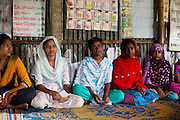 "Mony Mala (16, 3rd from left) speaks during a monthly meeting of a Children's Group in Bhashantek Basti (Slum) in Zon H, Dhaka, Bangladesh on 23rd September 2011. Mony says, ""I'm still a child, not prepared to be a wife. I feel pained that my parents don't see a point in educating me just because I'm a girl. I feel terrible when we are not able to stop a child marriage because the elders do not listen to us."" The Bhashantek Basti Childrens Group is run by children for children with the facilitation of PLAN Bangladesh and other partner NGOs. Slum children from ages 8 to 17 run the group within their own communities to protect vulnerable children from child related issues such as child marriage. Photo by Suzanne Lee for The Guardian"