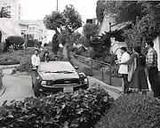 People sitting up in a car coming down Lombard Street with other people watching.