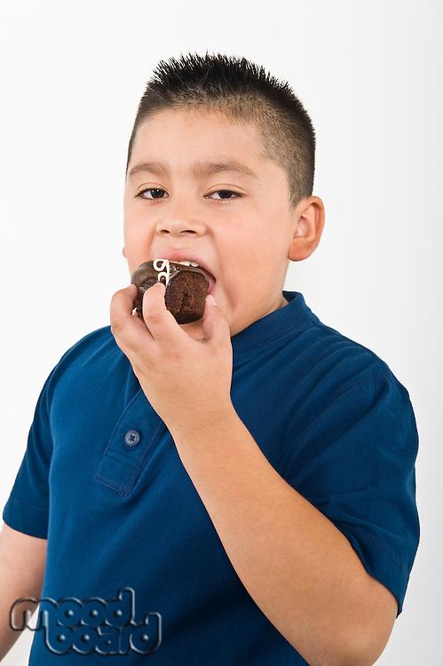 Pre-teen (10-12) boy eating cookie