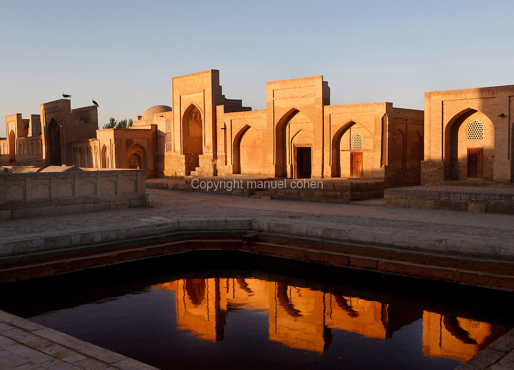 Low angle view of the Necropolis of the Memorial complex of Chor-Bakr, 16th century, Bukhara, Uzbekistan, pictured on July 10, 2010, reflected in a pool by the late afternoon light.  Bukhara, a city on the Silk Route is about 2500 years old. Its long history is displayed both through the impressive monuments and the overall town planning and architecture.