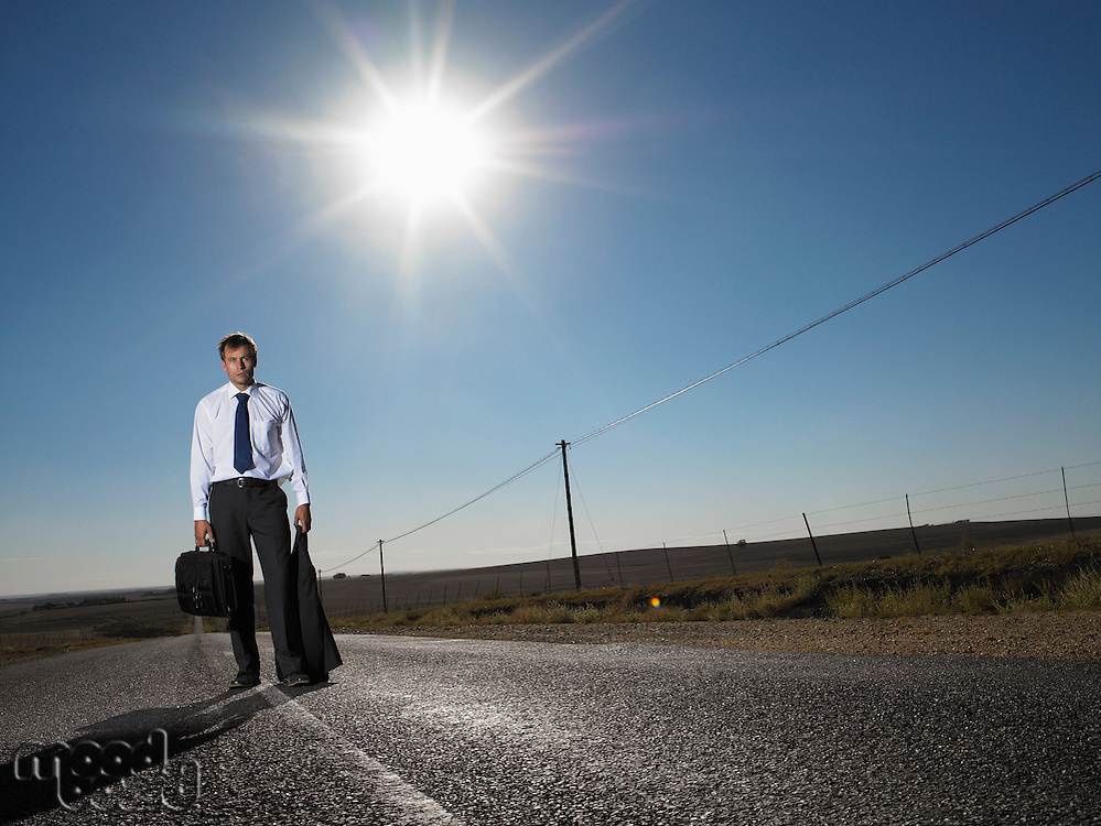 Businessman standing in middle of deserted road