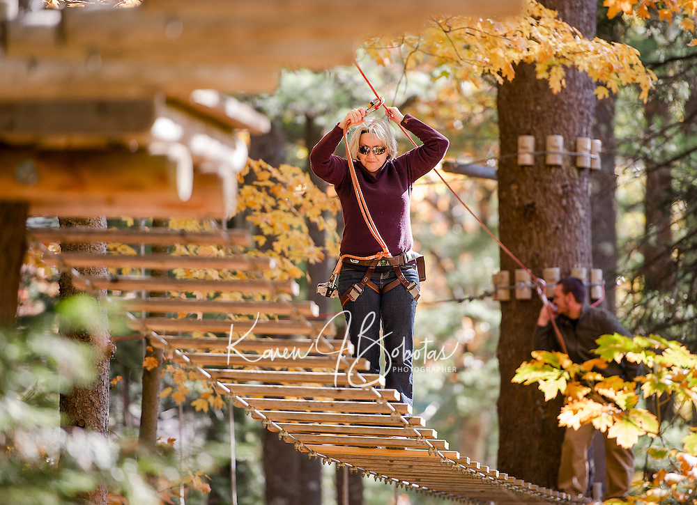 Pauline Nadeau and Jeff Potvin work their way through Gunstock's Aerial Treetop Adventure Ropes Course with the Wounded Warrior group on Monday afternoon.  (Karen Bobotas/for the Laconia Daily Sun)